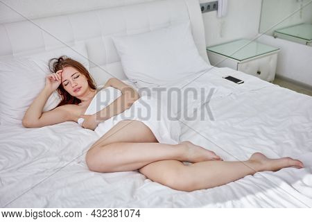 Woman Wrapped In Towel Is Resting On Bed In Bedroom.