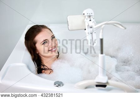 Mounting Hands Free Smartphone Holder On Bathtub In Bathroom, Young Woman Is Taking Bath And Watchin