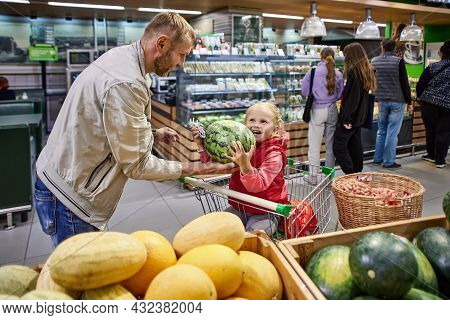 Father And Little Daughter Are Choosing Watermelon In Supermarket.