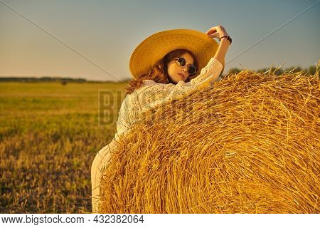 Modern boho, hippie style. Fashion model in knitted sweater, wide-brimmed straw hat and round glasses poses by a haystack in the setting sun. Autumn.