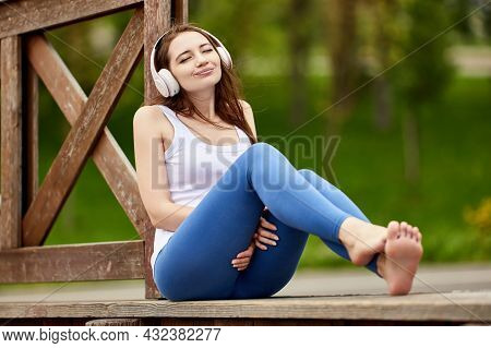 Woman In Wireless Headphones Closed Her Eyes While Listening To Music In Nature.