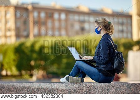 Young Woman Uses Laptop To Work Remotely Outdoors During Coronavirus Lockdown.