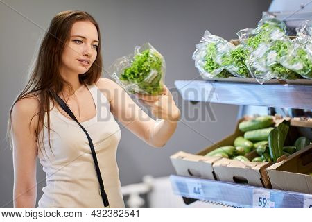 Woman In Her 30s Chooses Salad In Supermarket.