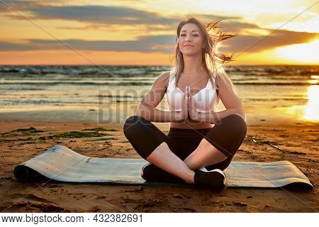 Yoga In Front Of Sea Sunset, Woman In Her 30s Does Exercise On Beach.