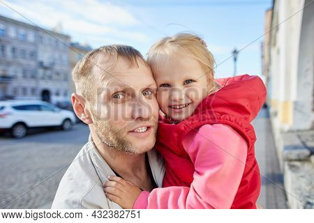 Mature Caucasian Man And Little Smiling Girl In His Arms.
