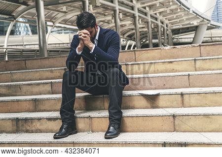 Businessman Bankruptcy And Debt With Hands Cover Face While Sitting On The Stairs.unemployed Busines