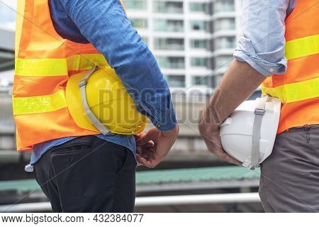 Teamwork Concept. Two Architect Construction Man Holding Safety Hardhat Helmet In Their Hands While