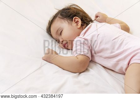 Little Baby Girl 12 Months Wearing Pink Cloth Sleeping On White Bed At Home. Adorable One Year Old T