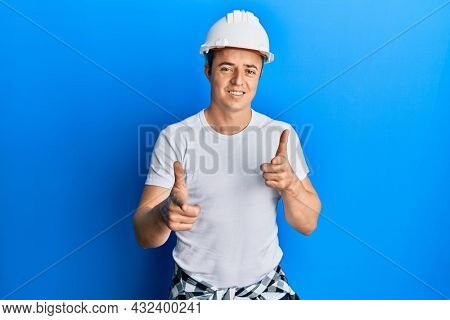 Handsome young man wearing builder uniform and hardhat pointing fingers to camera with happy and funny face. good energy and vibes.