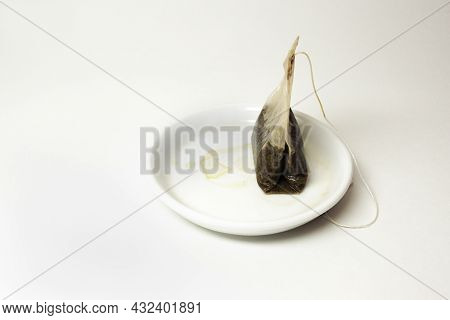 Used Tea Bag With A Long Thread, On Small White Saucer With Tea Stains