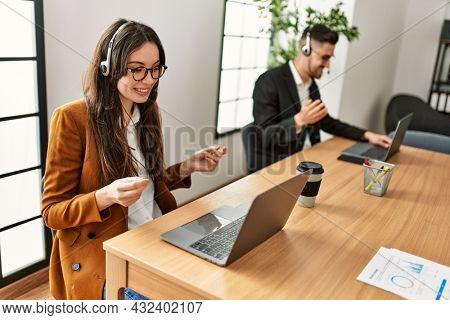 Two hispanic call center agents working at the office.