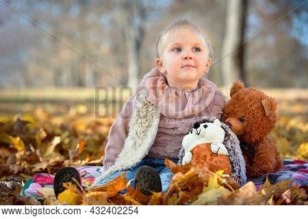 Little Beautiful Dreamy Caucasian Girl With Earrings In Autumn Park Sits In Golden Autumn Leaves Wit