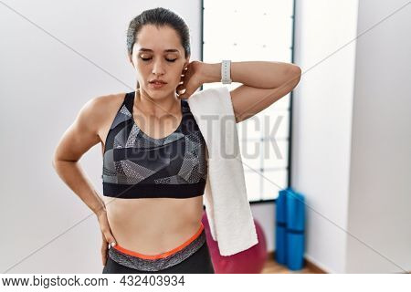 Young brunette woman wearing sportswear and towel at the gym suffering of neck ache injury, touching neck with hand, muscular pain