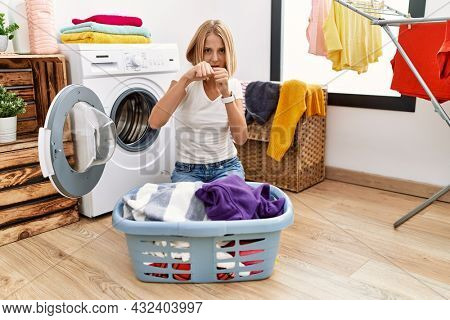 Young caucasian woman doing laundry with clothes in the basket punching fist to fight, aggressive and angry attack, threat and violence