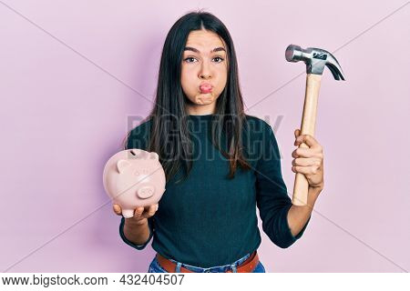 Young brunette woman holding piggy bank and hammer puffing cheeks with funny face. mouth inflated with air, catching air.