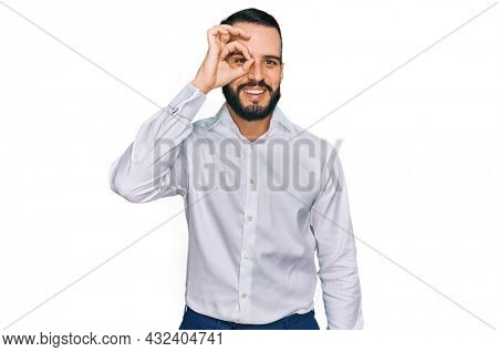 Young man with beard wearing business shirt doing ok gesture with hand smiling, eye looking through fingers with happy face.