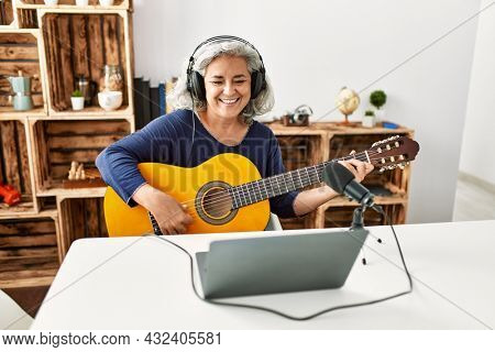 Middle age grey-haired woman playing guitar working at radio studio.