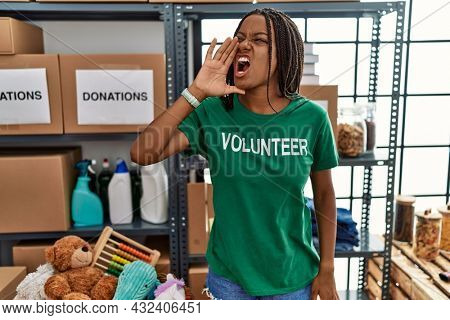 Young african american woman working wearing volunteer t shirt at donations stand shouting and screaming loud to side with hand on mouth. communication concept.