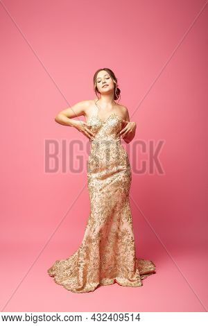 Full-length Portrait In Motion Of Beautiful, Radiant Woman In Long Shining Beige Dress And Hands Ris