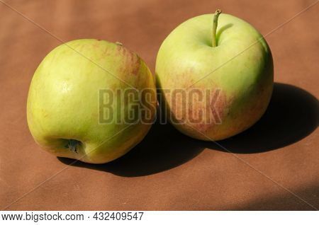Minimalist Composition With Apples On A Brown Background. Ripe Ready-to-eat Fruit In Bright Sunlight