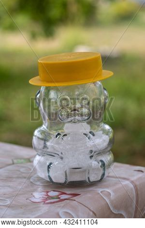 A Glass Salt Shaker In The Shape Of A Bear In A Yellow Hat, Standing On The Edge Of The Table On A B