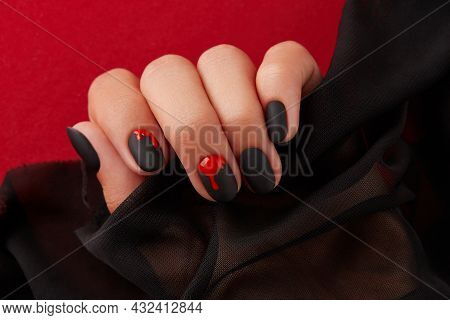 Close Up Womans Hand With Halloween Manicure On Red Background Holding Fabric. Manicure, Pedicure Be