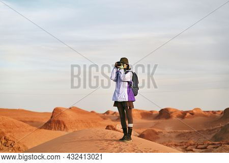 Asian Woman Photographer Standing In A National Geological Park Taking A Picture