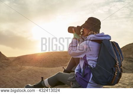 Asian Woman Female Photographer Taking A Photo Of Landscape In Gobi Desert With Yardang Landforms At