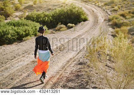 Rear View Of An Beautiful Asian Woman Walking On Dirt Road In Gobi Desert