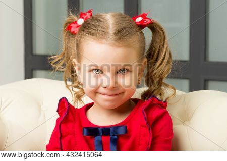 Cute Blonde Little Girl Sitting On Comfy Armchair. Charming Lovely Kid With Cute Ponytails Hairstyle