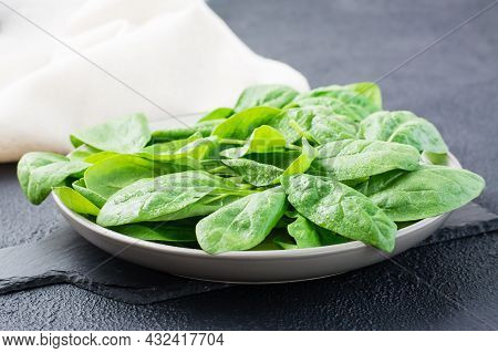 Fresh Baby Spinach Leaves In Drops Of Water On A Plate On A Slate Board On A Black Background. Veget