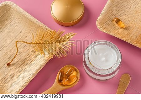 White Skin Care Cream In An Open Glass Jar, Few Essential Oil Capsules In A Wooden Spoon And Golden