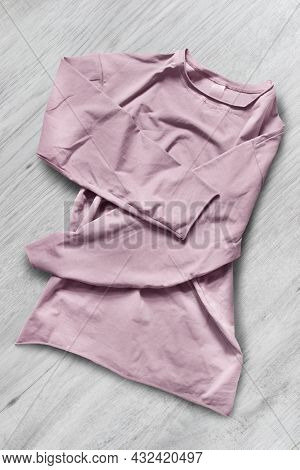Folded Pink Basic Cotton Shirt On White Wood Background