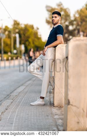 Man In Modern Clothes Posing While Leaning On A Wall Outdoors