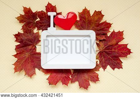 Autumnal Composition. Frame, I Love, With Heart And Red Maple Leaves On Pastel Yellow Background. Au