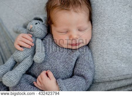 Newborn baby boy wearing in knitted costume sleeping and holding toy bunny. Infant kid studio portrait with decoration