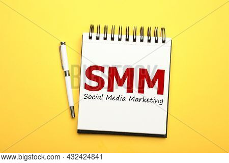 Notebook With Text Smm (social Media Marketing) And Pen On Yellow Background, Flat Lay