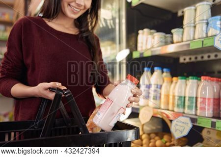 Young woman putting bottle with milk product to shopping basket in food store. Concept of shopping. Partial view of beautiful smiling brunette girl. Idea of healthy eating