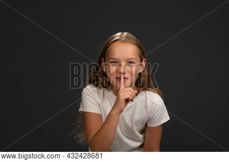 Saying To Keep Silence Little Girl Holds Her Finger On Her Lips Telling Everyone. Child Wearing Whit