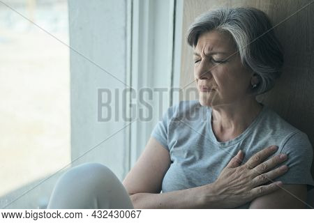 Elderly Senior Sick Disabled, Sad Woman In Pain And Suffering Sitting By The Window In The Hospital.