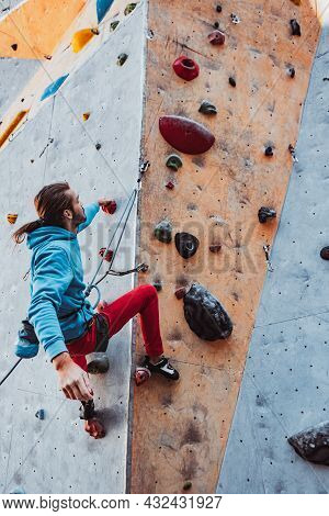 Young Man Professional Rock Climber Practicing At Training Center In Sunny Day, Outdoors. Concept Of
