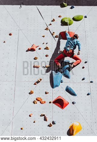 One Caucasian Man Professional Rock Climber Workouts At Training Center In Sunny Day, Outdoors. Conc