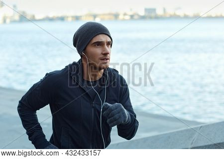 European runner running at city quay. Young sportsman wearing hat, hooded zipper sweatshirt and mittens. Man prepare to sport run competition. Person listening music in earphones. Daytime