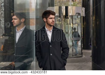 Young serious european businessman standing by glass building in city. Concept of modern successful man. Bearded stylish guy with hands in pockets wearing coat. Daytime