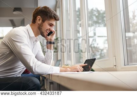 Young smiling european businessman talking on mobile phone and using digital tablet. Concept of modern successful man. Bearded stylish guy wearing formal clothes. Office interior. Daytime