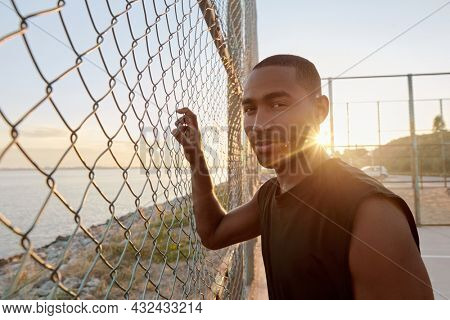 Young serious african sportsman standing at mesh fence on sports court. Black man wearing sportswear and looking at camera. Urban basketball player. Sea behind mesh fence. Sunny daytime
