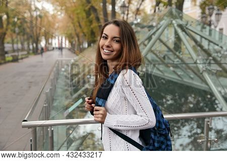 Smiling european female student going with backpack in city. Young beautiful girl wearing knitted sweater and looking in camera. Blurred background of glass building. Autumn daytime