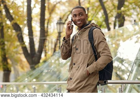 Smiling black male student standing with hand in pocket and talking on mobile phone. Young african man wear parka coat and backpack. Blurred glass building in city on background. Autumn daytime