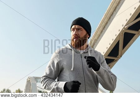 Concentrated european man running on iron bridge. Young sportsman wear hat, hooded zipper sweatshirt and mittens. Man prepare to sport run competition. Sunny daytime
