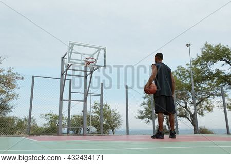 Young african sportsman standing with ball and looking on basketball hoop on sports court. Back bottom view of black man with towel wear sportswear and sneakers. Urban basketball player. Cloudy day